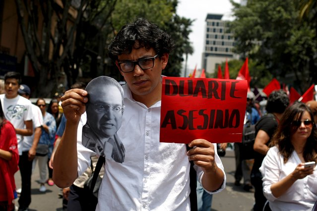 "A demonstrator holds a photo of Veracruz Governor Javier Duarte and a placard reading ""Duarte murderer"" during a protest against the murder of photojournalist Ruben Espinosa and four other women in Mexico City, August 16, 2015. Espinosa, a prominent Mexican news photographer was among five people found dead in a middle-class neighborhood of the capital on July 31, 2015. (Photo by Tomas Bravo/Reuters)"