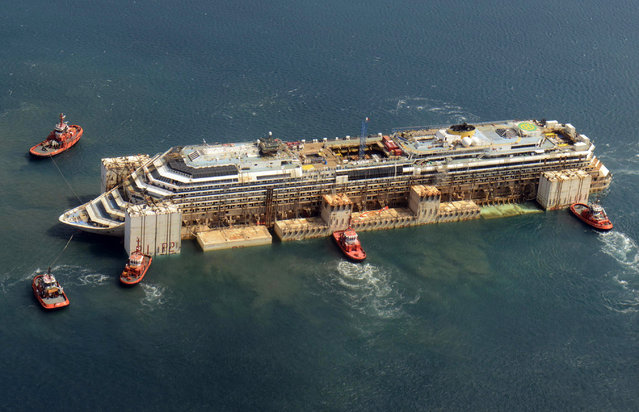A handout photo made available by the Italian CoastGuards of an aerial view as the Costa Concordia undertakes one of her docking manoures in the harbour of Genoa, July 29, 2014. She will gradually move to her final resting place before being reduced to scrap. (Photo by EPA/Italian Coastguards)