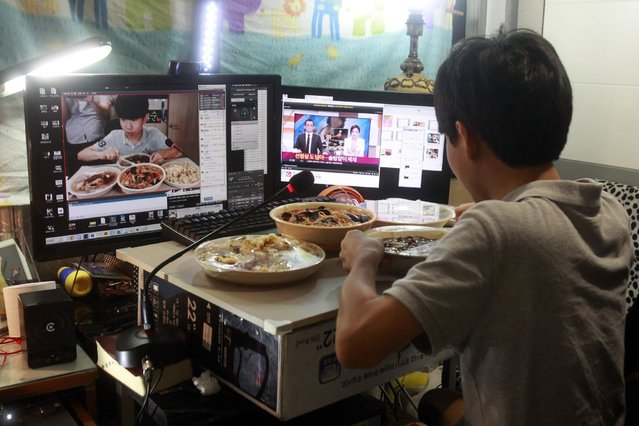 In this Monday, August 17, 2015 photo, Kim Sung-jin, 14, broadcasts himself eating delivery Chinese food in his room at home in Bucheon, south of Seoul, South Korea. Every evening, he gorges on food as he chats before a live camera with hundreds, sometimes thousands, of teenagers watching. (Photo by Julie Yoon/AP Photo)