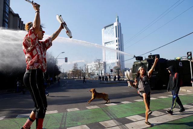 Jugglers perform on a street as a police water canon releases a jet of water on demonstrators during an unauthorized march called by the Chilean student federations to protest against government's education reform, in Santiago, Chile July 5, 2016. (Photo by Ivan Alvarado/Reuters)