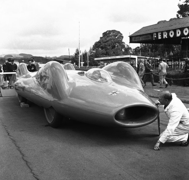 Leo Villa, Donald Campbell's Chief Mechanic, looks into the air intake of the jet powered car bluebird on the Goodwood Motor Racing Circuit in Sussex, England on July 18, 1960, where the new car is being prepared for trials, now scheduled for Thursday, July 21. After preliminary trials in Britain, the bluebird will be shipped to America for a world record attempt on the Bonneville Salt Flats in Utah. (Photo by AP Photo/PRI)