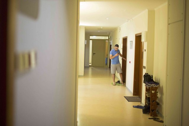 """Syrian migrant Eyad Ibrahim Aghe uses a mobile phone in the corridor of the  """"Sharehaus Refugio"""" community in Berlin, where Germans and migrants live together, Germany August 19, 2015. (Photo by Axel Schmidt/Reuters)"""