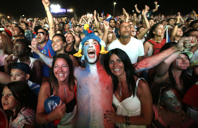 French supporters celebrate France's victory in the Marseille fan zone after the Euro 2016 semifinal soccer match between Germany and France,Thursday, July 7, 2016 in Marseille, southern France. France won 2-0. (Photo by Claude Paris/AP Photo)
