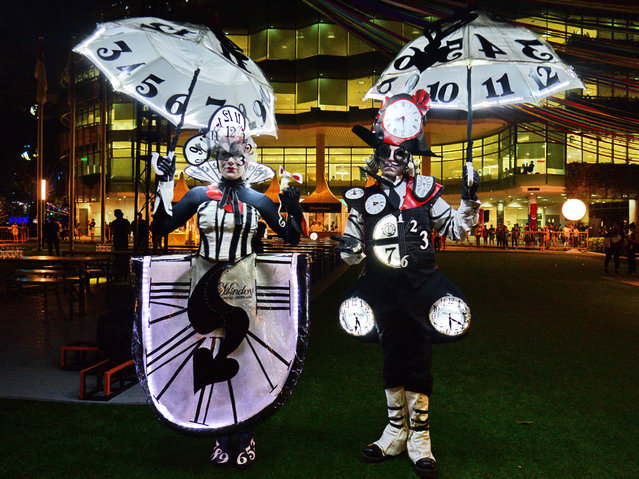 "Australian performers illuminated with real clocks titled ""The Time Minder"" attend a media preview of the Night Festival in Singapore on August 23, 2017. Singapore's arts and heritage district will be transformed into Singapore largest outdoor performing arts festival to celebrate its 10th year edition Night Festival from August 24 to 26. (Photo by Roslan Rahman/AFP Photo)"