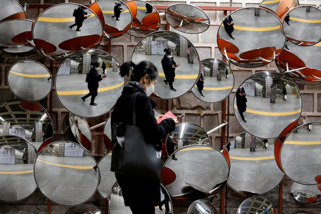 A woman wearing a mask to prevent the coronavirus is reflected in the mirrors, in Seoul, South Korea, February 24, 2020. (Photo by Heo Ran/Reuters)