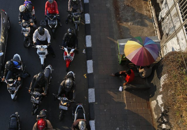 Snack vendors under an umbrella wait for customers as motorists are caught in a traffic jam during rush hour in Jakarta, Indonesia, Tuesday, August 4, 2015. (Photo by Dita Alangkara/AP Photo)
