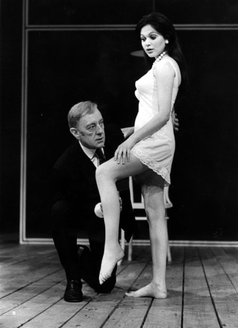 """Sir Alec Guinness (1914–2000) examines a patient, played by Madeleine Smith, in the stage play """"Habeas Corpus"""" by Alan Bennett. 9th May 1973. (Photo by Central Press)"""