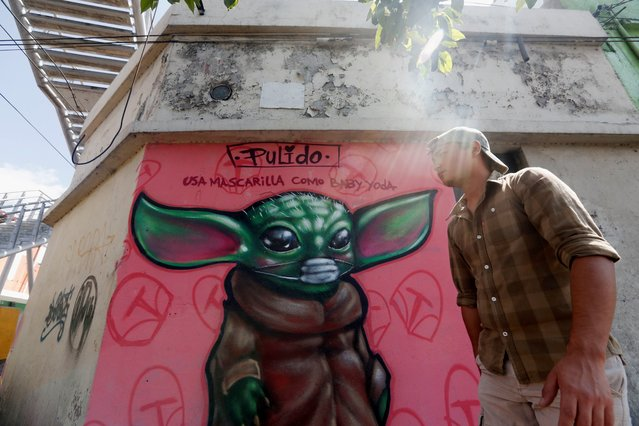 """View of a graffiti drawn by artist """"Pulido"""" for the character Baby Yoda, from the TV series """"The Mandalorian"""", wearing a mask and the message """"wear mask like baby Yoda"""" to remind the population to take measures against the coronavirus, in Guatemala City, Guatemala, 30 March 2020. Guatemalan President announced a day earlier the extension of the 12-hours-a-day curfew for two more weeks in Guatemala, where 36 people have been diagnosed with COVID-19. (Photo by Esteban Biba/EPA/EFE)"""