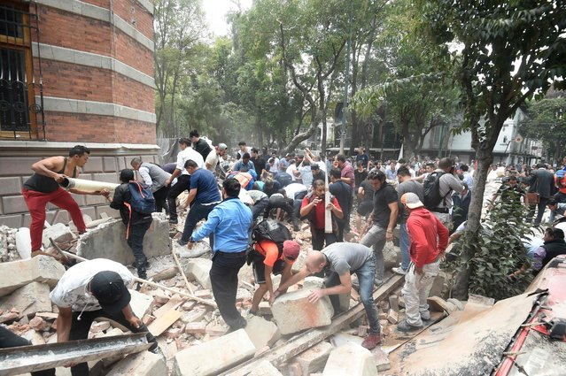 People remove debris of a damaged building after a real quake rattled Mexico City on September 19, 2017 while an earthquake drill was being held in the capital. A powerful earthquake shook Mexico City on Tuesday, causing panic among the megalopolis' 20 million inhabitants on the 32nd anniversary of a devastating 1985 quake. The US Geological Survey put the quake's magnitude at 7.1 while Mexico's Seismological Institute said it measured 6.8 on its scale. The institute said the quake's epicenter was seven kilometers west of Chiautla de Tapia, in the neighboring state of Puebla. (Photo by Alfredo Estrella/AFP Photo)