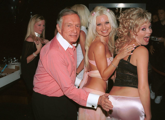Hugh Hefner spanks playboy models Izabella Kasprzyk and Bridget Marquardt during their birthday dinner party at Joya restaurant on September 25, 2002 in Beverly Hills, California. (Photo by David Klein/Getty Images)