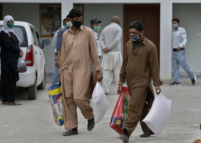 Daily wages workers carry sacks of wheat flour and other food supplies provided for free by a municipally, during a lockdown to try to contain the outbreak of the coronavirus, in Islamabad, Pakistan, Monday, April 6, 2020. (Photo by Anjum Naveed/AP Photo)