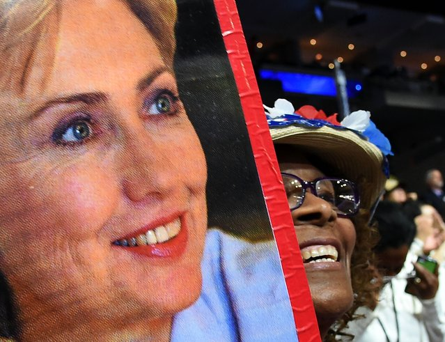 A delegate holds a photo of US Democratic Presidential Candidate Hillary Clinton during the final day of the 2016 Democratic National Convention on July 28, 2016, at the Wells Fargo Center in Philadelphia, Pennsylvania. (Photo by Robyn Beck/AFP Photo)