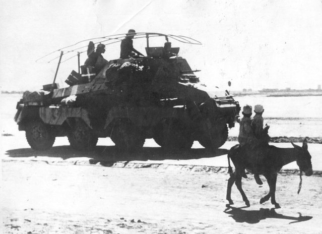 Two Libyan boys travelling on an a*s turn to stare at a passing German tank in the desert near Tripoli. 1st December 1942. (Photo by Keystone)