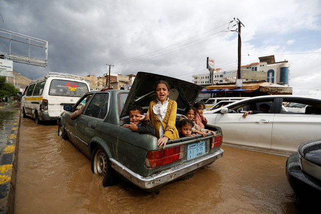 Children ride in the trunk of a car on a flooded street in Sanaa, Yemen August 1, 2016. (Photo by Khaled Abdullah/Reuters)