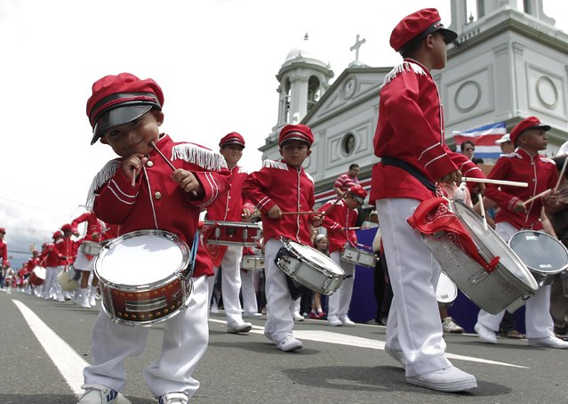 A child with his drum smiles as he walks near students performing during a parade commemorating Costa Rica's Independence Day  in San Jose September 15, 2014. Schools and colleges participated in parades throughout the country to celebrate its 193rd anniversary of independence. (Photo by Juan Carlos Ulate/Reuters)