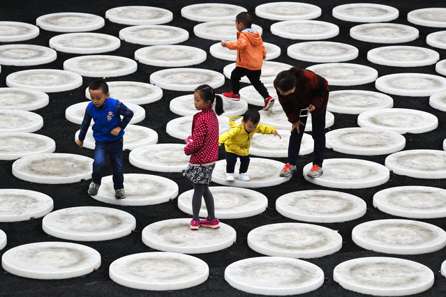 A woman watches as children play on the lights circle on display at the capital city's popular shopping mall in Beijing, Sunday, October 22, 2017. (Photo by Andy Wong/AP Photo)