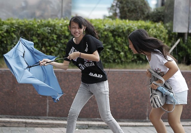 Girls holding umbrella walk against strong winds as tropical storm Fung-wong hits Taiwan, in Taipei September 21, 2014. (Photo by Pichi Chuang/Reuters)