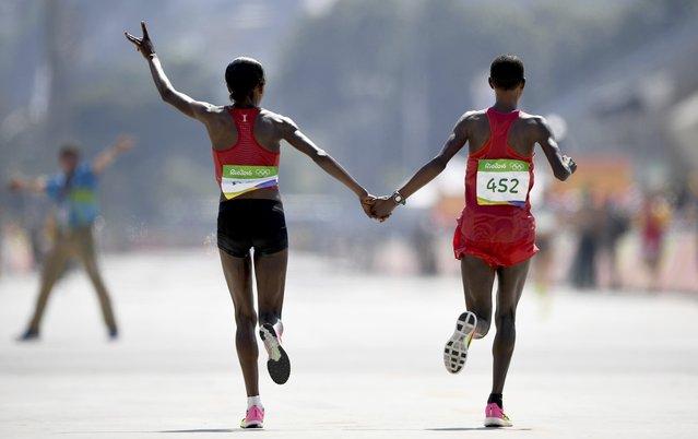 2016 Rio Olympics, Athletics, Final, Women's Marathon, Sambodromo, Rio de Janeiro, Brazil on August 14, 2016. Jemima Sumgong (KEN) of Kenya and Eunice Jepkirui Kirwa (BRN) of Bahrain celebrate after the race. (Photo by Dylan Martinez/Reuters)