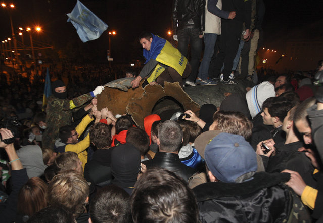 Activists dismantle Ukraine's biggest bronze monument to Lenin at a pro-Ukrainian rally  in a central square of the eastern city of Kharkiv, Ukraine, Sunday, September 28, 2014. (Photo by Sergey Kozlov/AP Photo)