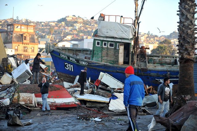 People recover items from destroyed houses next to a ship dragged by the waves after a earthquake hit areas of central Chile, in Coquimbo city, north of Santiago, Chile, September 17, 2015. (Photo by Mauricio Ubilla/Reuters)