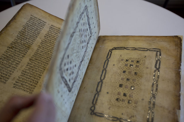 In this photo taken Sunday, October 5, 2014, a library official shows a Jewish manuscript smuggled into Israel from Damascus in a Mossad spy operation in the early 1990s in Jerusalem. (Photo by Sebastian Scheiner/AP Photo)
