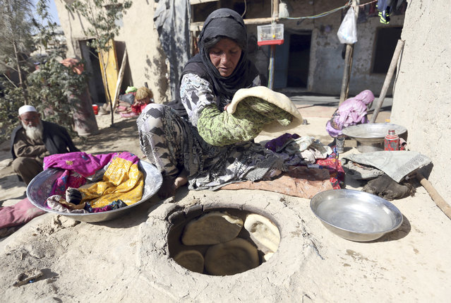 An Afghan internally displaced woman prepares traditional bread at her home on the outskirts of Kabul, Afghanistan, Monday, October 30, 2017. The war-torn country faces the challenges of poverty, unemployment, and a lack of infrastructure. (Photo by Rahmat Gul/AP Photo)
