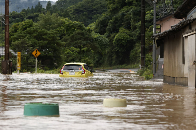 A car is stuck in a flooded road by heavy rain in Yatsushiro, Kumamoto prefecture, southwestern Japan, Saturday, July 4, 2020. The Japan Meteorological Agency raised the heavy rain warnings in many parts of the prefectures to the highest level shortly before 5 a.m. It was the first time for the agency to do so in the two prefectures, Kumamoto and Kagoshima. (Photo by Kyodo News via AP Photo)
