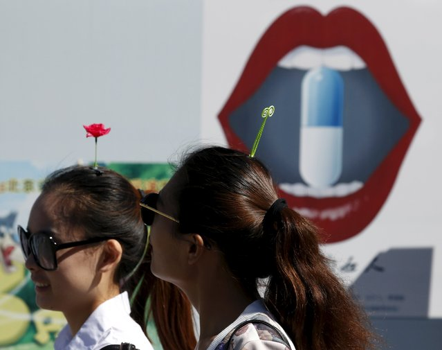 Women wearing flower and sprout-like hairpins walk past an advertisement board in Beijing, China, September 25, 2015. (Photo by Kim Kyung-Hoon/Reuters)