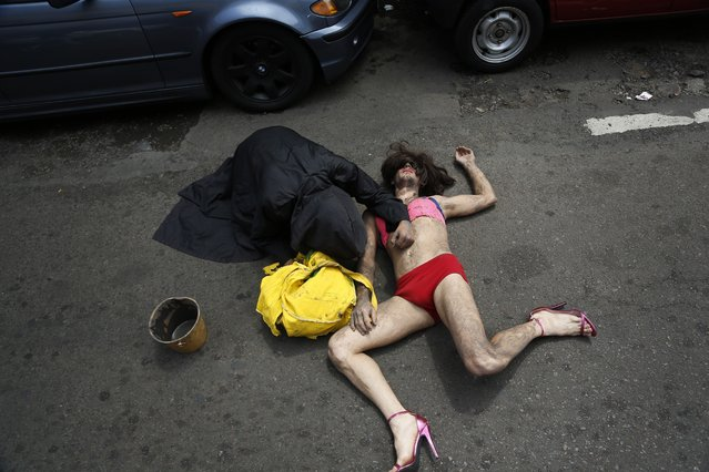 In this September 30, 2017 photo, Stelio Barbosa lies on the street to perform the murder of a transvestite during the annual LGBQT parade in Asuncion, Paraguay. Gay rights groups say the ban on teaching sexual diversity in schools goes against Paraguay's constitution because it is discriminatory. (Photo by Jorge Saenz/AP Photo)