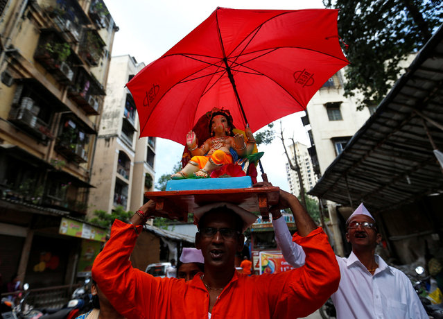 A devotee carries an idol of the Hindu god Ganesh, the deity of prosperity, to a place of worship on the first day of the Ganesh Chaturthi festival in Mumbai, India, September 5, 2016. (Photo by Danish Siddiqui/Reuters)