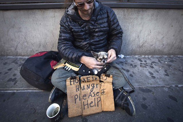 John Stewart caresses his dog Cuddles as he sits on 14th Street with a sign asking for help in New York October 27, 2014. Stewart has been homeless for 2.5 years and can't find a bed in a shelter because he refuses to give up his dog who he has had for 20 years. (Photo by Carlo Allegri/Reuters)