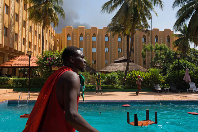 A protestor walks past a pool as protestors ransack the Azalai Hotel in  Burkina Faso as people protest  against their longtime president  Blaise Compaore who is seeking  another term in Ouagadougou, Burkina Faso, Thursday, October 30, 2014. (Photo by Theo Renaut/AP Photo)