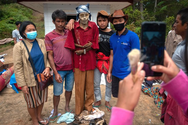 """Family members taking foto with preserved body of their relative during a traditional ritual called """"Manene"""" in Panggala, Nort Toraja, South Sulawesi, Indonesia, Tuesday, August 25th 2020. (Photo by Hariandi Hafid/ZUMA Wire/Rex Features/Shutterstock)"""