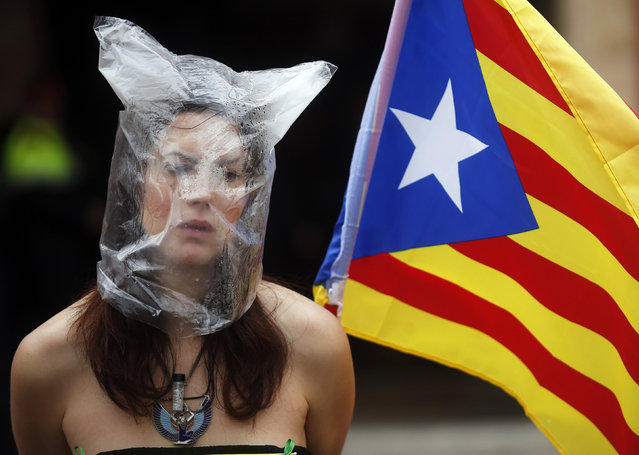 A pro-independence protester sits in front of Catalonia's regional parliament as lawmakers vote inside, in Barcelona, January 16, 2014. (Photo by Albert Gea/Reuters)