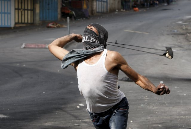 A Palestinian uses a slingshot against Israeli troops during clashes in the West Bank city of Hebron October 10, 2015. Tensions have surged in 11 days of violence in which four Israelis and 17 Palestinians - including several Palestinians shot by police, have been killed in Jerusalem, the Israeli-occupied West Bank, Gaza and in Israeli cities. (Photo by Mussa Qawasma/Reuters)