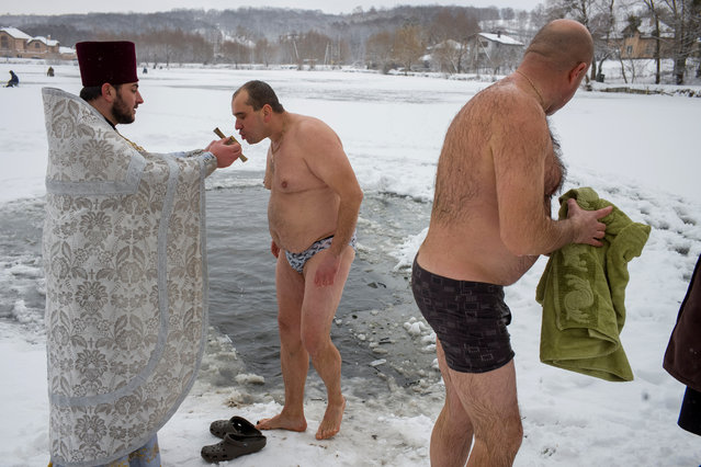 A priest takes part in a religious ceremony as men take a dip in icy water during Orthodox Epiphany celebrations in the village of Ivankovychi, Ukraine on January 19, 2018. (Photo by Gleb Garanich/Reuters)