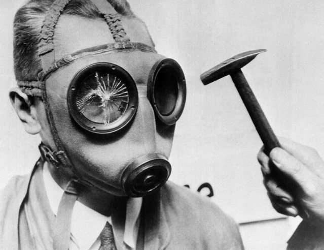 This experiment was recently conducted to illustrate the new non-breakable glass which is being fitted into gas masks, October 19, 1932 in Germany. Sale of these masks is common in the markets of Berlin, and many of them sold for domestic animals. They are produced to fit tightly, and gas lessons are given in many places. (Photo by AP Photo)