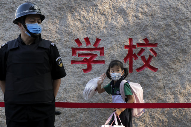 A student wearing a face mask to help curb the spread of the coronavirus waves next to a masked security guard as she arrives to a primary school in Beijing, Monday, September 7, 2020. Students in the capital city returned to school on Monday in a staggered start to the new school year because of the coronavirus outbreak. (Photo by Andy Wong/AP Photo)