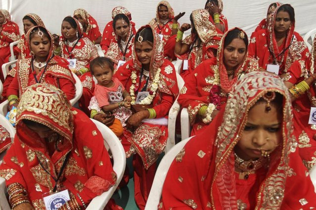 An Indian bride, center, holds a child as she sits with other brides during a mass marriage of 162 Muslim couples in Ahmadabad, India, Sunday, March 3, 2013. Mass marriages in India are organized by social organizations primarily to help the economically backward families who cannot afford the high ceremony costs as well as the customary dowry and expensive gifts that are still prevalent in many communities. (Photo by Ajit Solanki/AP Photo/LaPresse)