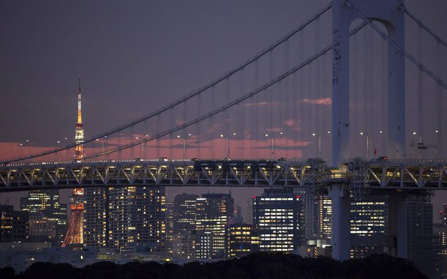 The Tokyo Tower stands illuminated behind the Rainbow Bridge seen from the Odaiba Marine Park which will host Triathlon and Aquatics (10km Marathon Swimming) during the 2020 Olympics on July 24, 2019 in Tokyo, Japan. (Photo by Tomohiro Ohsumi/Getty Images)