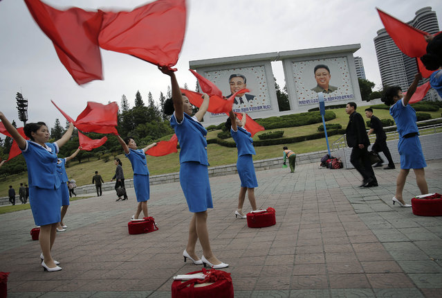 North Korean women stand near portraits of their late leaders Kim Il Sung, left, and Kim Jong Il and wave flags cheering on their fellow countrymen as they start their day during morning rush hour on Wednesday, September 28, 2016, in Pyongyang, North Korea. Women's League units are out in force these days in front of subway entrances and other strategic locations to dance and wave red flags as loud patriotic music blares from boom boxes. Sometimes they are joined by middle school brass bands in their morning ritual, which is intended to encourage workers to start their day off with more vigor. (Photo by Wong Maye-E/AP Photo)
