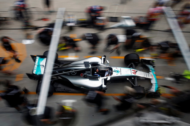 Formula One, F1, Malaysia Grand Prix, Sepang, Malaysia on September 29, 2016. Crew members push the car of Mercedes' Lewis Hamilton of Britain for a change of tyres. (Photo by Edgar Su/Reuters)