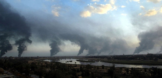 Palls of black smoke from raging oil fires billow over Baghdad, on March 27, 2003. The oil-filled trenches were set off by Iraqis to try and block the visibility of U.S. warplanes and missiles. (Photo by Goran Tomasevic/Reuters/The Atlantic)