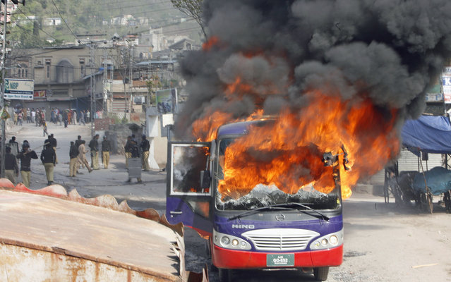 A bus set ablaze by angry protesters during a demonstration against power outage in Muzffarabad, capital of Pakistan-administrated Kashmir March 21, 2013. People protesting against power outage in Muzaffarabad turned violent on Thursday. Around 50 people, including a police official, sustained minor injuries when the protesters pelted stones at the police and burnt a police bus, local media reported. (Photo by Amiruddin Mughal/Reuters)