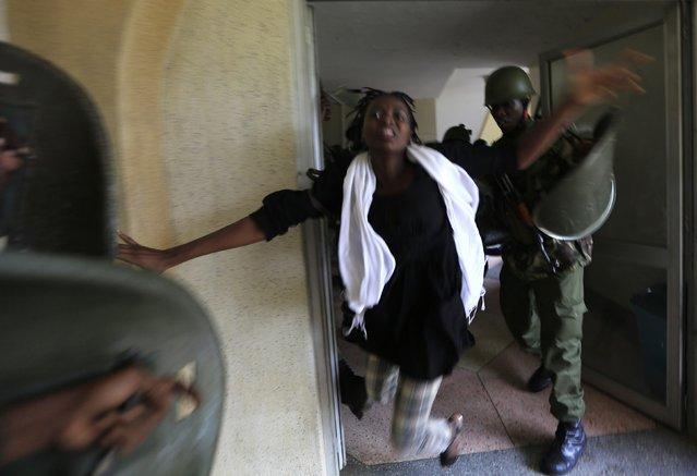 A riot policeman uses a baton to hit a rioting University of Nairobi student in Kenya's capital Nairobi, in this May 20, 2014 file photo. (Photo by Noor Khamis/Reuters)
