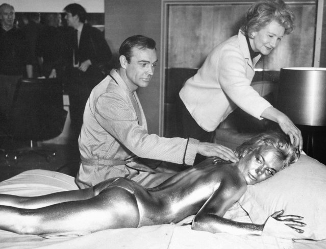 "In this file photo dated April 20, 1964, James Bond, alias, Sean Connery, finds himself in a sticky situation with actress Shirley Eaton at Pinewood Studios, near London.  Miss Eaton was given a liberal coating of gold paint for a scene in the latest Bond thriller ""Goldfinger"", with unidentified woman at top. Scottish actor Sean Connery, considered by many to have been the best James Bond, has died aged 90, according to an announcement from his family. (Photo by Victor Boynton/AP Photo)"