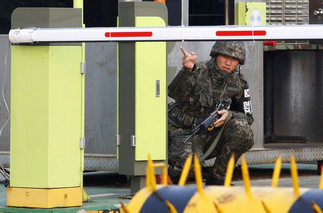 A South Korean Army soldier gestures at a military check point in Paju, South Korea, near the border village of Panmunjom, Thursday, April 4, 2013. North Korea on Wednesday barred South Korean workers from entering a jointly run factory park just over the heavily armed border in the North, officials in Seoul said, a day after Pyongyang announced it would restart its long-shuttered plutonium reactor and increase production of nuclear weapons material. (Photo by Ahn Young-joon/AP Photo)