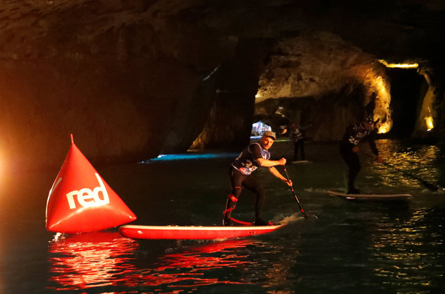 Competitors paddle during a Stand Up Paddle (SUP) race of the Alpine Lakes Tour, on Europe's biggest underground lake, in St-Leonard, Switzerland, March 10, 2018. (Photo by Denis Balibouse/Reuters)