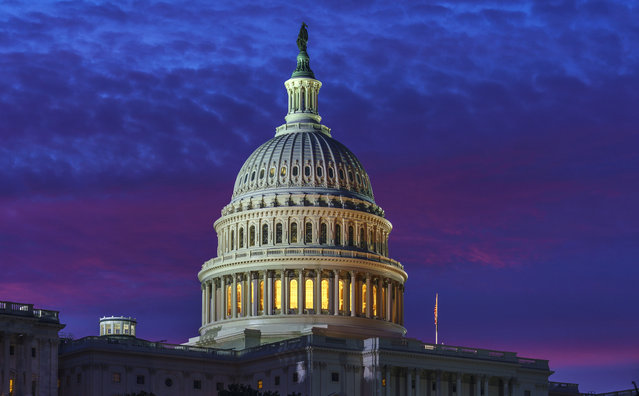 In shades of red and blue, dawn arrives on Capitol Hill in Washington, Friday, November 6, 2020. (Photo by J. Scott Applewhite/AP Photo)