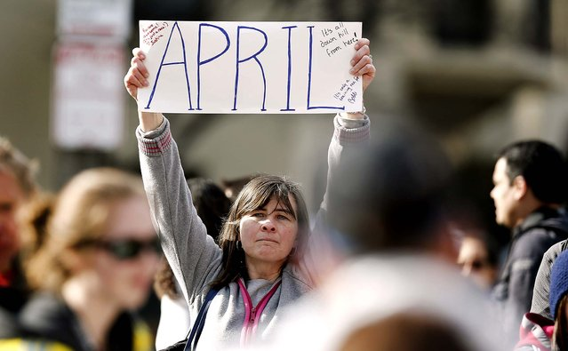 Justine Franco of Montpelier, Vt., holds up a sign near Copley Square, looking for her missing friend, April, who was running in her first Boston Marathon. (Photo by Winslow Townson/Associated Press)
